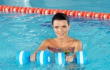 девушка с гантелями в воде