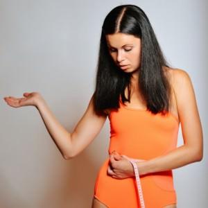 девушка измеряет талию