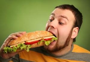 мужчина ест гамбургер