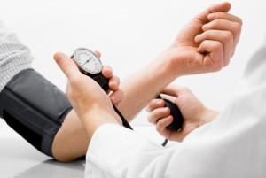 врач измеряет давление у пациента