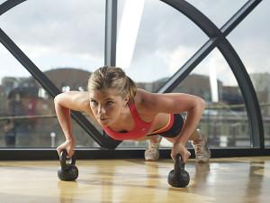 девушка делает упражнения с гирями