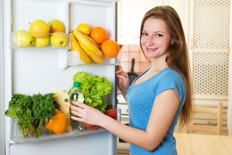 девушка берет воду из холодильника