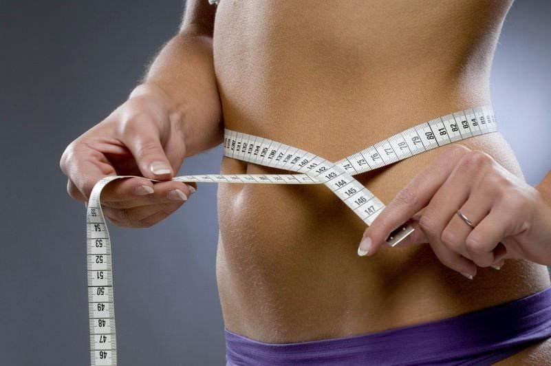девушка измеряет размер талии